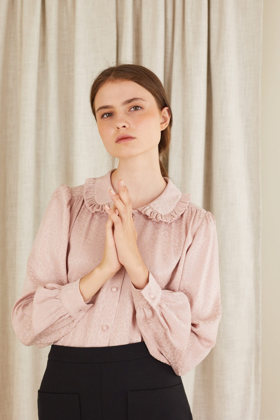 pink shirt with ruffles on the collar