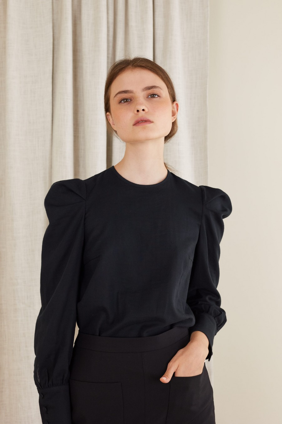 black blouse with sculptural sleeves