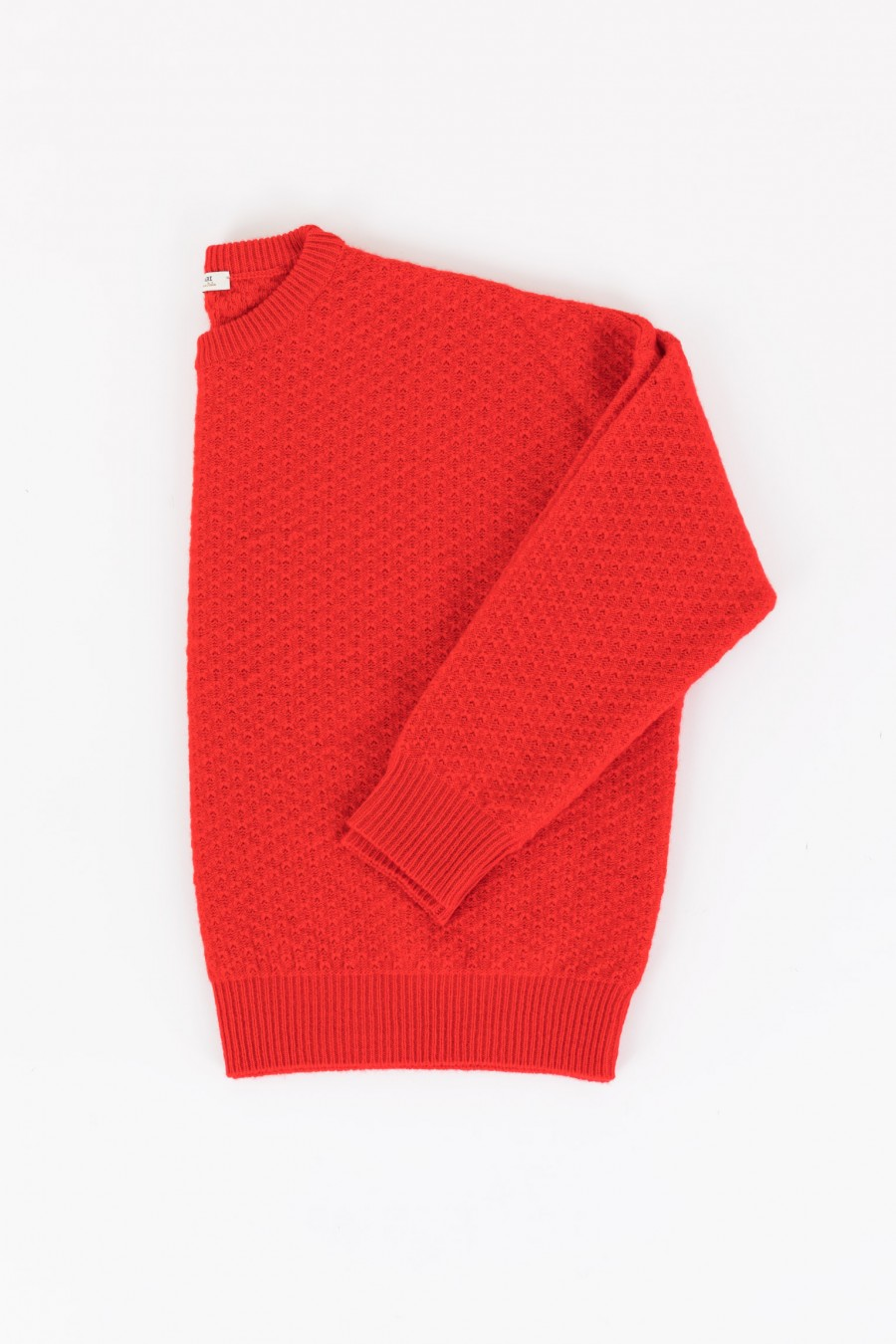 Red jumper in open-worked knitting
